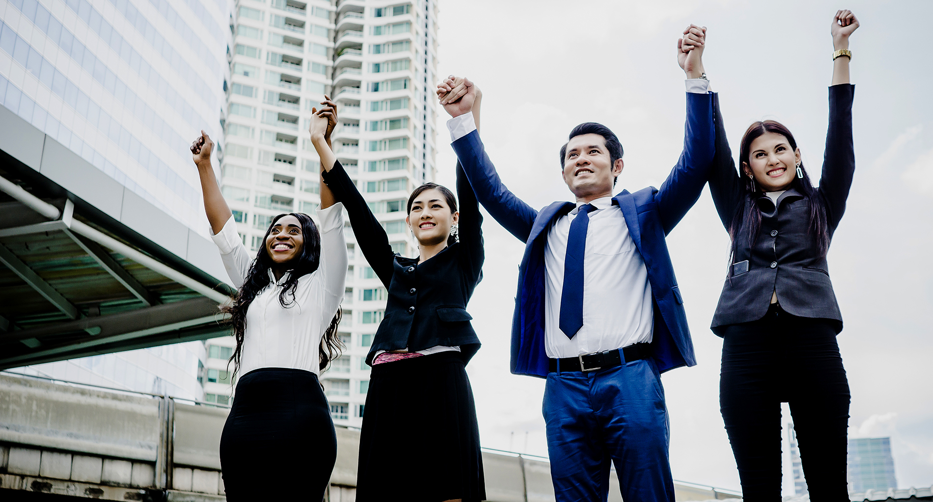 Group of Happy young business people with hands in the air succe